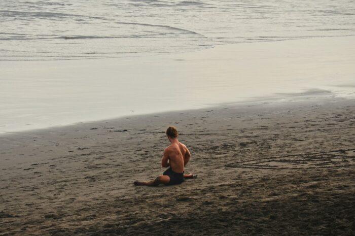 Mladík sedí na pláži, protože ho chytili svalové křeče.